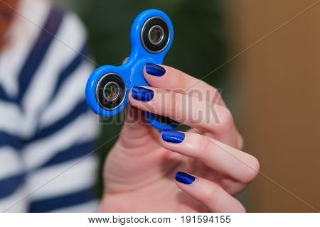 A girl is holding a popular toy fidget spinner in her hands. Stress relief. Anti stress and relaxation fidgets spinner for tired people. Girl playing with a fidget spinner.
