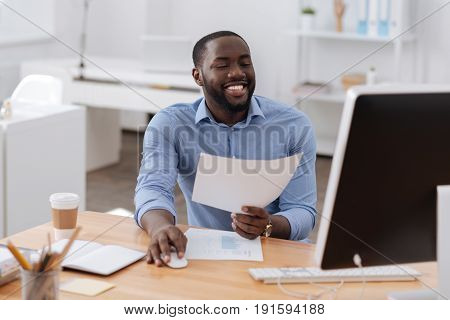 Modern workplace. Positive happy nice man holding a computer mouse and working on the computer while holding a document