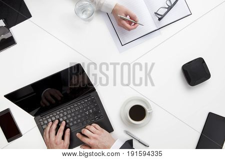 Overhead view of business people working at white office desk