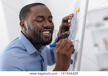 Visual material. Joyful pleasant good looking man standing near the whiteboard and using a highlighter while drawing a scheme