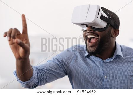 Age of technologies. Delighted happy nice man wearing 3d glasses and smiling while using innovative technologies
