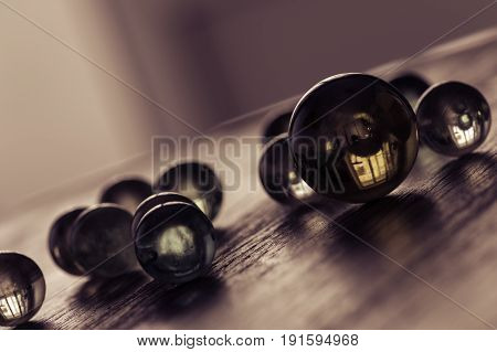 Glass balls on a wooden surface at an angle. Stylish artistic work. Selective focus. Chocolate tinting.