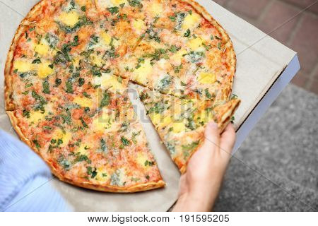 Man taking slice of pizza from box, closeup