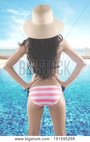 Summer Concept. Back view of a young woman with long hair and beautiful body standing near a swimming pool while wearing a striped swimsuit and straw hat. Shot with beach view