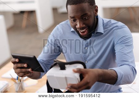 Technological advances. Joyful happy exited man sitting at the table and looking at the virtual reality glasses while holding a tablet