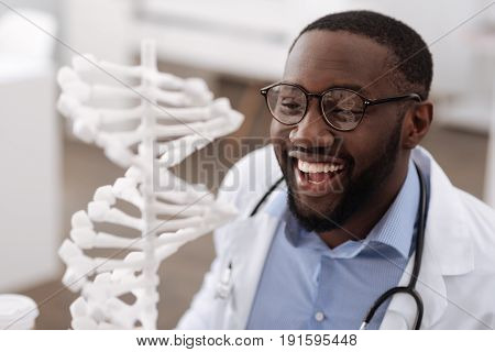 Genetic science. Smart modern male scientist smiling and looking at the gene model while being in the laboratory