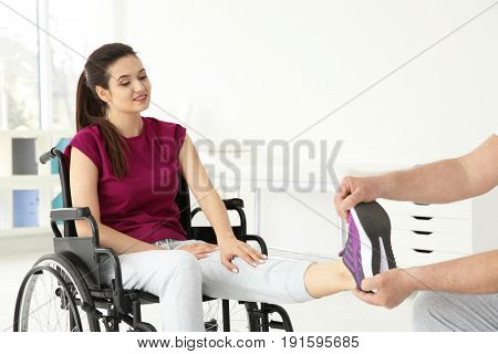 Young disabled woman with senior orthopedist in rehabilitation clinic