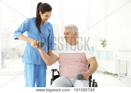 Senior disabled man with young orthopedist in rehabilitation clinic