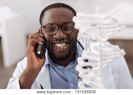 Conversation with a colleague. Cheerful nice positive scientist looking at the gene model and smiling while speaking on the phone with his colleague
