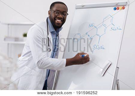 Organic chemistry. Delighted smart afro american man writing a formula and smiling while studying organic chemistry