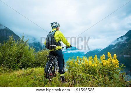Mountain bike cyclist near fjord, summer Norway