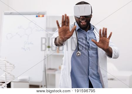 Innovation in treatment. Handsome professional male doctor pressing his hands to the virtual screen and learning about new medical innovations while wearing 3d glasses