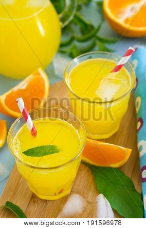 Sweet orange drink with ice cubes and mint leaves