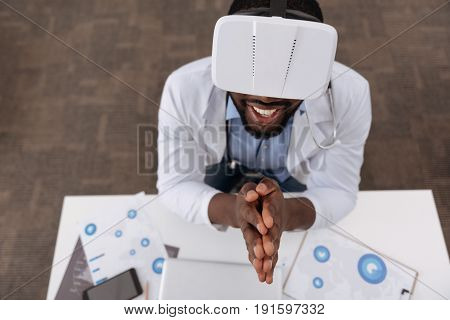Modern advances. Nice delighted joyful man wearing 3d glasses and holding his hands together while enjoying being in the virtual reality