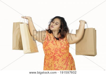 Portrait of fat woman holding shopping bags while lifting hands isolated on white background