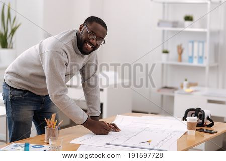 Modern construction. Cheerful positive nice engineer leaning over his drawings and working while designing a modern building