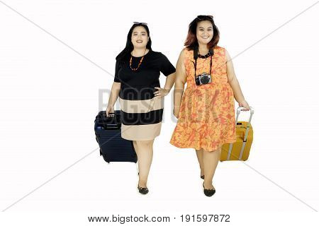 Full length of two fat women walking while carrying suitcase isolated on white background