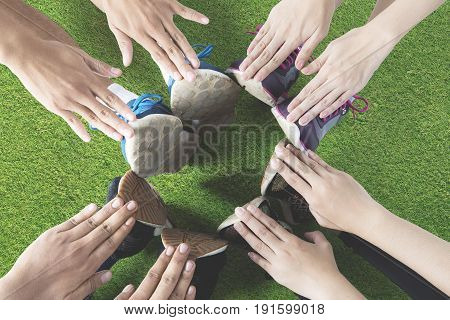 Top view of group of friends sitting on green grass making a circle with their hands and feet after workout