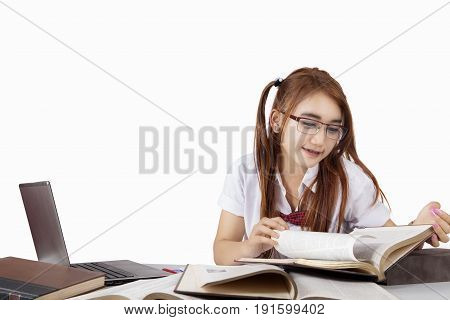 Female high school student preparing for exam by studying and reading book on the table isolated on white background