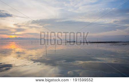 Sunrise at Pak Pra lakePattalungThailand. Silhouette of traditional fishing methodfisherman. reflection.non focus and blur.
