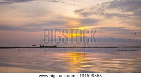 Sunrise at Pak Pra lakePattalungThailand. Silhouette of traditional fishing methodfisherman.