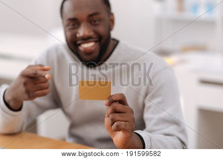 Non cash payments. Selective focus of a credit card being held by a nice positive cheerful man while using an electronic banking