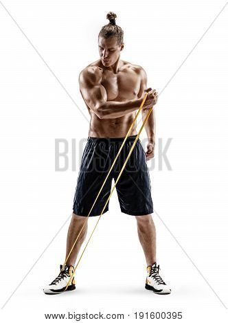 Young strong man performs exercises using a resistance band. Photo of muscular male isolated on white background. Strength and motivation. Full length