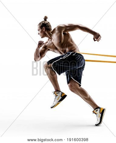 Muscular man runner in silhouette using a resistance band in his exercise routine. Photo of young male performs fitness exercises isolated on white background. Side view