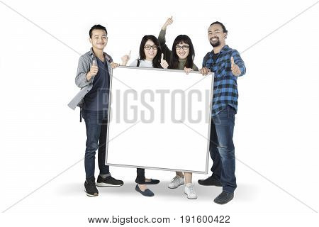 Group of multiracial students showing thumbs up while holding a blank whiteboard isolated on white background