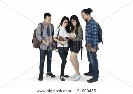 Group of multiracial students carrying a backpack while using a digital tablet together isolated on white background