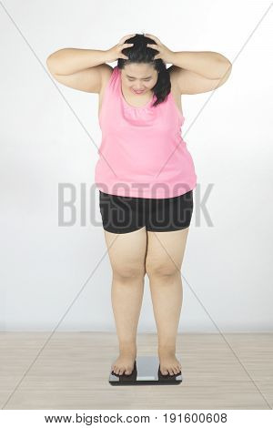 Obese woman holding her head and depressed after fail to lose weight while looking at weight scale