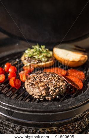 Delicious cheeseburger with tomatoes cooking on hot flaming grill. Barbecue. Restaurant