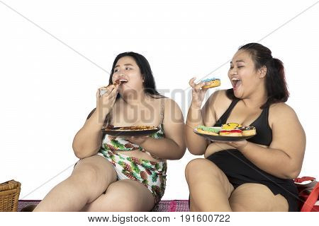 Two obese women enjoying their holiday while eating a plate of donuts isolated on white background