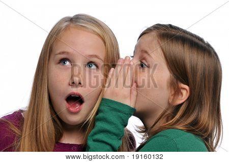 Dos chicas contar un secreto y expresando sorpresa aislado en blanco