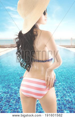 Summer Concept. Rear view of a young woman with beautiful body standing near a swimming pool while wearing a striped bikini sun glasses and straw hat