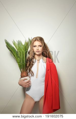 Beautiful young woman in swimming suit with exotic plant on light background