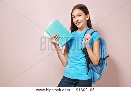 Cute pretty girl with books and schoolbag on color background