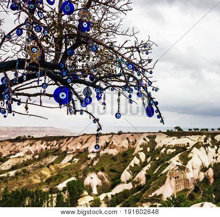 Mountain valley landscape Uchisar, Cappadocia, Turkey. Tree with traditional blue evil eyes - popular Turkish souvenir