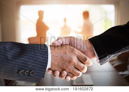 businessmen handshaking in a meeting room.acquisition concept with vintage tone.