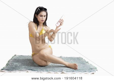 Beautiful young woman wearing bikini and using sunblock isolated on white background