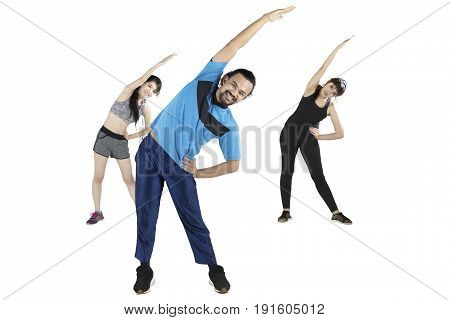 Young people doing stretching exercise together while lifting hands isolated on white background