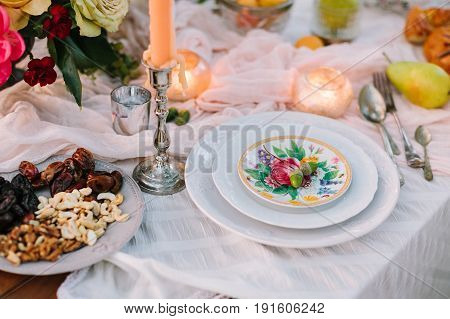 wedding, decor, setting, vegetarianism, lifestyle concept - still-life of table linens with snow white draping, plates with floral print, candles, silver tableware, bunch of flowers and nuts