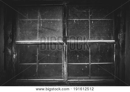 Black and white picture of the old dirty window and dust on the web