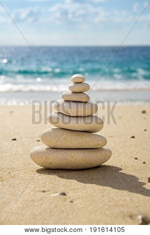 Stacked tower of balancing smooth stones on the sand of a tropical beach with the ocean behind symbolic of longevity luck and happiness.