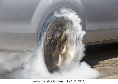 race car burns rubber off its tires in preparation for the race .