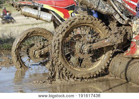 Enduro wheel in muddy track,climb wood obstacle