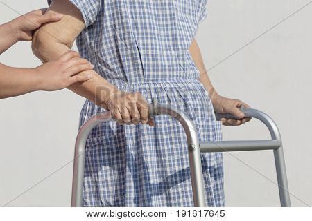 senior woman using a walker with caregiver.