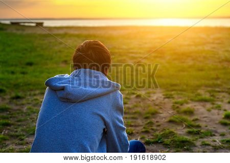 Lonely Young Man on the Nature at Sunset