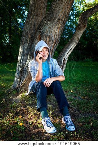 Cheerful Teenager with Cellphone under the Tree