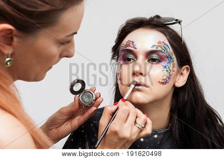Make-up artist applying mascara on a creative make up. Beauty and fashion. Creativity and makeup. Cosmetics and backstage preparation for photo shooting